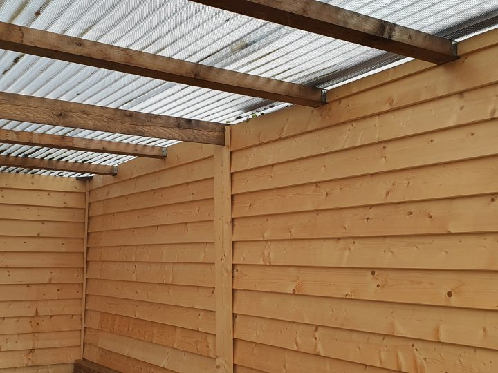Holzbekleideter Carport mit PVC-Wellplatten